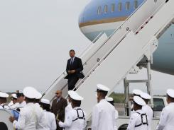 President Obama walks down the stairs of Air Force One as a Colombian military band stands in formation upon his arrival Friday in Cartagena, Colombia.