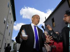 Newark Mayor Cory Booker's right hand is bandaged as he stands between a boarded-up 433 Hawthorne Ave., right, and his home in Newark on Friday. Booker rescued his neighbor Thursday from a fire at the home.