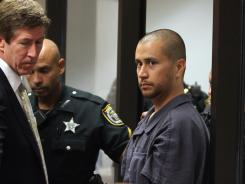 George Zimmerman, center, who has been charged with second-degree murder in the shooting death of 17-year-old Trayvon Martin, is directed by a Seminole County deputy and by his attorney Mark O'Mara during a court hearing Thursday in Sanford, Fla.