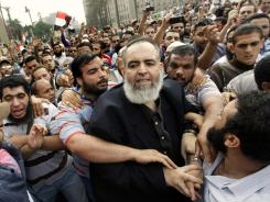 Hazem Salah Abu Ismail, center, is guarded by his supporters as he enters Tahrir Square in Cairo on Oct. 28.