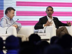 Colombia's President Juan Manuel Santos, left, sits next to President Obama who spoke on Saturday to an audience gathered at the CEO Summit of the Americas in Cartagena, Colombia.
