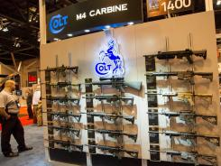 A wall shows Colt M4 Carbines at the NRA convention on Saturday in St. Louis.