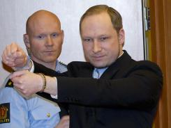 Norwegian right-wing extremist Anders Behring Breivik, right, arrives in court in Oslo on Feb. 6.