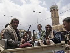 Yemeni policemen sit in a pickup truck in front of Sanaa's International airport in Yemen on April 8.