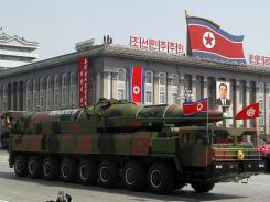 A North Korean vehicle carrying a missile passes by during a mass military parade Sunday in Pyongyang's Kim Il Sung Square.
