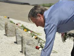 Ralph Badinelli, a Virginia Tech professor, places flowers on the 32 stone memorials for the victims of the April 16, 2007 campus shooting.