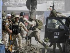 Afghan security forces rush to the site of an attack Sunday in Kabul.