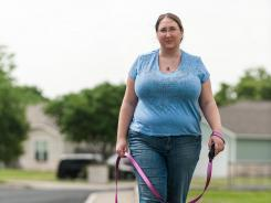 Dana Kendall takes her dog, Toni, for a walk in San Antonio. Kendall took dog training lessons at Animal Behavior College.