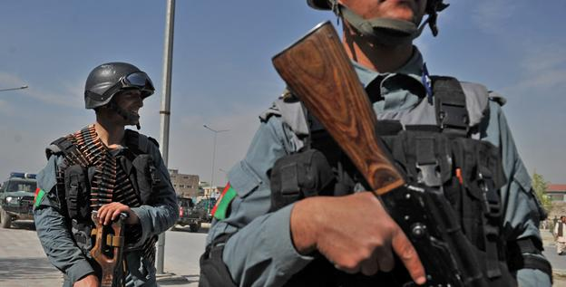 Afghan policemen stand guard near the building where Taliban fighters launched an attack in Kabul on Monday.