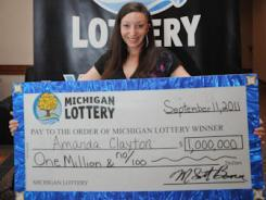 In this photo provided by the Michigan Lottery, Amanda Clayton holds her $1 million lottery check on March 8.