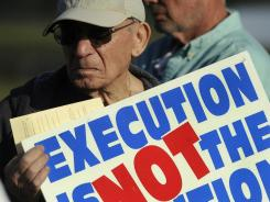 John Barbaro from Daytona Beach, Fla., holds a sign as he joined protesters demonstrating against the death penalty in front of the Florida state prison near Starke, Fla., where David Alan Gore was put to death April 12.