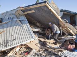 Tornado survivors: Richard Keith helps sister-in-law Mitzi Keith on Monday in Wichita. There were at least 120 reports of Midwest tornadoes this weekend, primarily in Kansas.