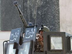 Prepared to return fire: A member of the Afghan security force at his station Sunday in Kabul.