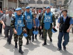 A handout picture released by the Syrian Arab News Agency (SANA) shows members of a U.N. monitors team as they visit a suburb of the Syrian capital of Damascus on Wednesday.