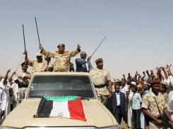 Sudanese President Omar al-Bashir, center, waves from the back of a truck during a visit to North Kordofan, Sudan.
