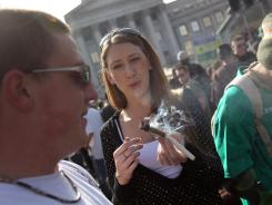 "A woman passes a joint at a pro-marijuana ""4/20"" celebration in front of the state capitol building April 20, 2010, in Denver."