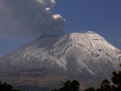 A plume of ash and smoke rises from the Popocatepetl volcano seen from the outskirts of the town of Santiago Xalizintla, Mexico, on Friday.