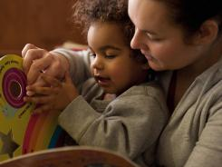 Kathleen Marshall reads with her toddler, Kevin, at their home in Philadelphia, where soil tests showed elevated levels of lead.
