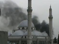 This image made from a video uploaded to YouTube on Thursday shows smoke rising from a mosque after reported shelling in Homs.