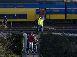 Care providers evacuate an injured passenger from a train after a collision Saturday in Amsterdam.