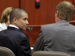 George Zimmerman, left, speaks with his attorney Mark O'Mara as he appears in court Friday in Sanford, Fla.