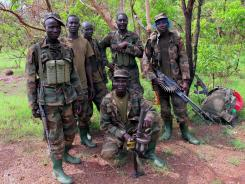 Ugandan soldiers hunting for fugitive warlord Joseph Kony relax after a 14-kilometerpatrol near the River Vovodo, Central African Republic, on Thursday.
