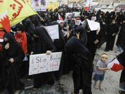 Anti-government protesters carry signs and national flags during a march Saturday in Diraz, Bahrain.