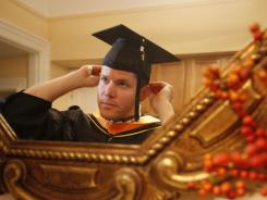 Corey Fry, a graduate from the University of California at San Francisco nursing school, tries on his cap and gown at his apartment on June 8, 2010.
