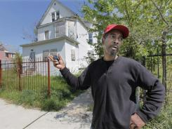 Antie Moore stands in front of the former home of Jennifer Hudson and her family in the Englewood neighborhood of Chicago on Tuesday.