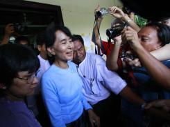 Myanmar opposition leader Aung San Suu Kyi, center, talks to the media as she leaves the National League for Democracy headquarters on Sunday.