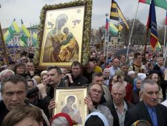Russian Orthodox believers hold flags and icons as they pray outside the Christ the Savior Cathedral in Moscow on Sunday.