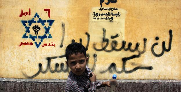 An Egyptian boy passes counter-revolution graffiti on the wall outside his school in Cairo on Sunday.