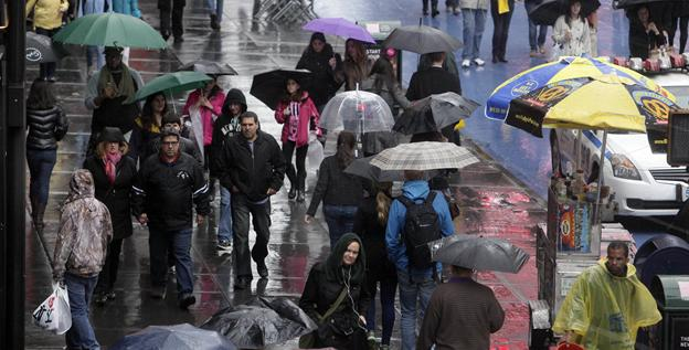 People walk through New York's Times Square on Sunday. A spring nor'easter is hitting the East Coast  and is expected to bring rain, heavy winds and even snow in some places.