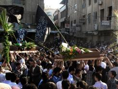Mourners carry the bodies of Adam al Najjar, an infant, and Free Syrian Army fighter Mowaffaq al Nablsi during their funeral Saturday in Douma, Syria.