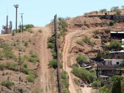 A fence on the southern U.S. border, separating Mexico, right, from Nogales, Ariz.