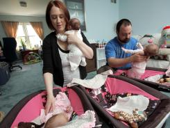 Candice and Michael Nigro, both 29, of Middletown, N.J., at home with their two-month-old triplets Emma, Michaela and Hailey April 21. Their daughters were the result of a second effort at invitro fertilization.