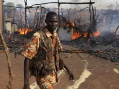 A policeman walks past the smoldering remains of a market in Rubkona, South Sudan, on Monday.