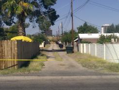 An alley behind the street where Isabel Mercedes Celis went missing from her home is cut off with police tape Sunday in Tucson.
