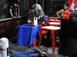The body of Brazilian journalist Decio Sa lies on the ground after being shot at a restaurant and bar in Sao Luis.