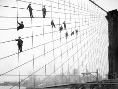 Painters are suspended from wires on the Brooklyn Bridge in New York on Oct. 7, 1914. Over 870,000 photos have been scanned and made available online.