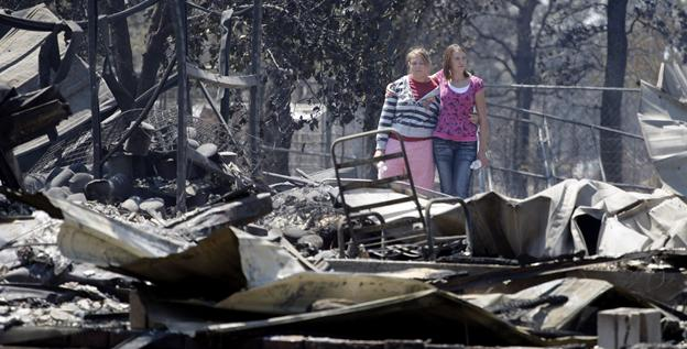 Sisters Laura, left, and Michelle Clements survey their fire-destroyed home on Sept. 6 in Bastrop, Texas.
