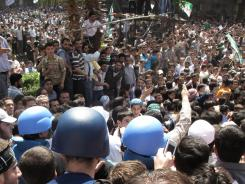Syrian protesters gather around U.N. observers during their visit in Douma, near the capital of Damascus, on Monday.