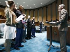Military personnel and civilians take the oath of citizenship administered by U.S. Citizenship and Immigration Services Director John Kramer, right, on Jan. 26 in Phoenix.