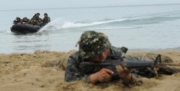 A member of the Philippine marines reconaissance team secures the beach as U.S. and Philippine marines arrive on a rubber boat during a beach raid simulation on Monday.