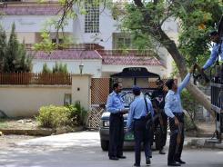 Pakistani policemen arrive for their guard shift outside the house where family members of slain Al-Qaeda chief Osama bin Laden are believed to be held in Islamabad on April 20.