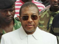 In 1997, Liberian presidential candidate and warlord Charles Taylor arrives at a polling center in Monrovia, Liberia.
