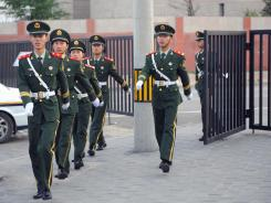 Chinese guards march out of the U.S. embassy compound in Beijing on Friday.