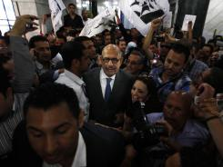 The Nobel Peace laureate Mohamed ElBaradei, center, is surrounded by supporters upon his arrival at a press conference Saturday to launch his new Constitution political party in Cairo.