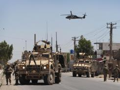 U.S. soldiers secure a street as a medevac helicopter flies above during an attack Saturday at the governor's compound in Kandahar, Afghanistan.