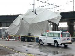 Officials respond to the scene where a tent blew over after high winds crossed the area on Saturday in St. Louis.